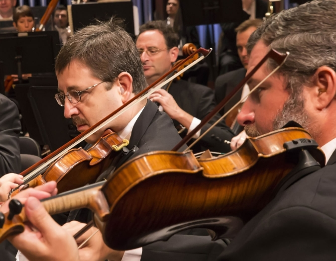 Image of Erik Berg and David Mastrangelo of the Naples Philharmonic on stage playing violins during a performance