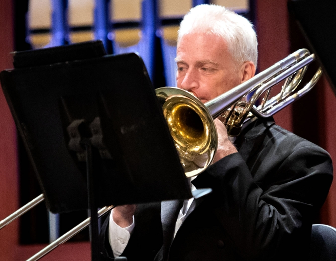 Image of Michael Zion of the Naples Philharmonic on stage playing a trombone during a performance
