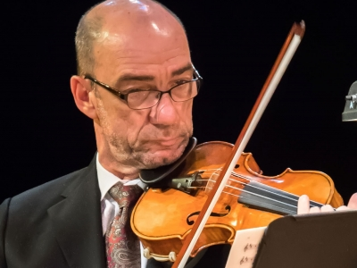 Image of Boris Sandler of the Naples Philharmonic on stage playing a violin during a performance