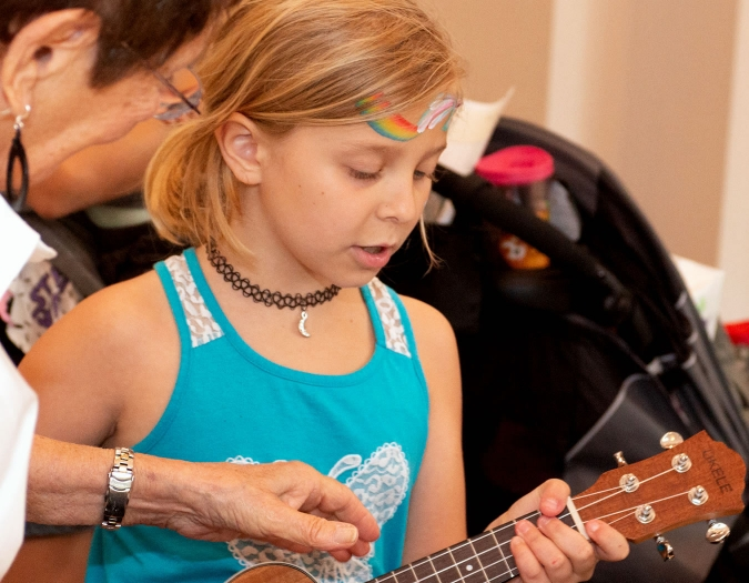 Image of a child playing a musical instrument during a Community Day event