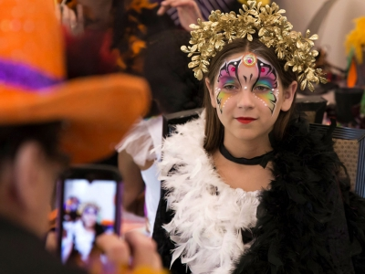 Image a child posing for the camera after receiving a crown and face painting