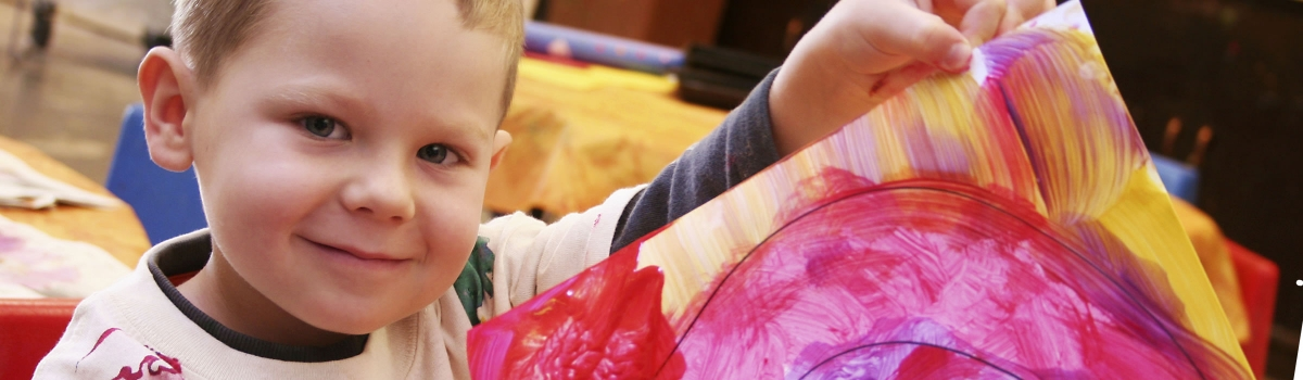 Image of very young child holding up art and smiling for the camera, proud of what he has created
