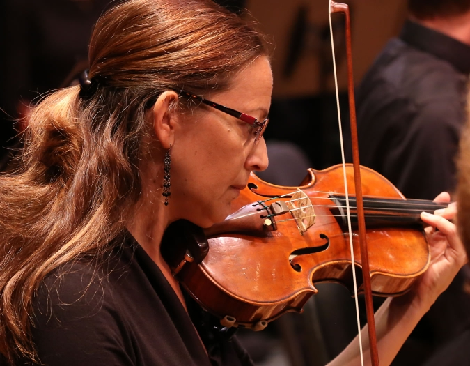 Image of Sania Whitaker of the Naples Philharmonic on stage playing a violin during a performance
