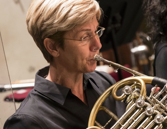 Image of Ellen Tomasiewicz of the Naples Philharmonic on stage playing a horn during a performance