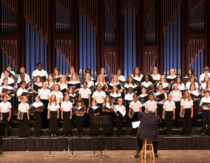 Image of student singers performing on stage during a concert of the Naples Philharmonic Youth Chorus