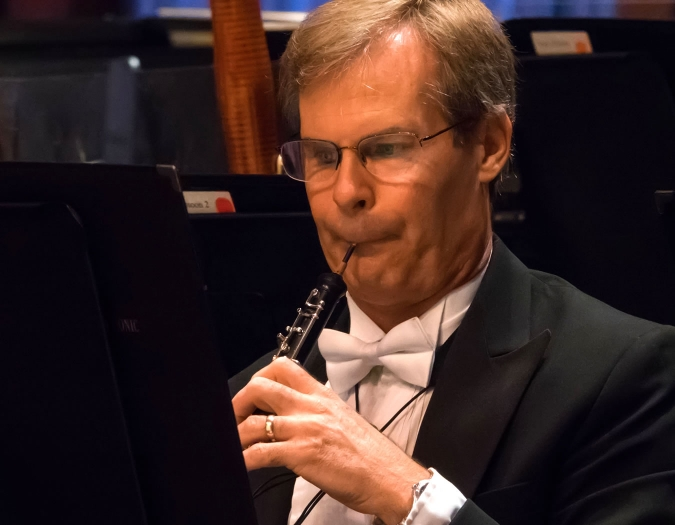 Image of Andrew Snedeker of the Naples Philharmonic on stage playing oboe during a performance