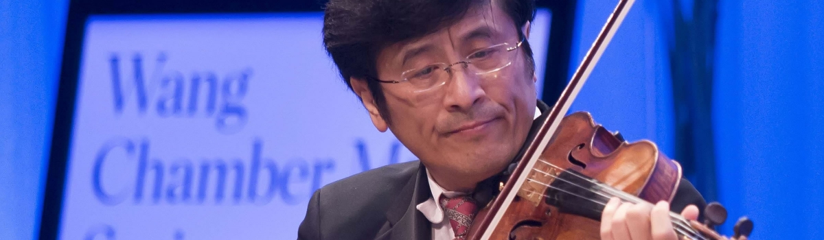 Image of James Zhang of the Naples Philharmonic on stage playing a violin during a Wang chamber music performance