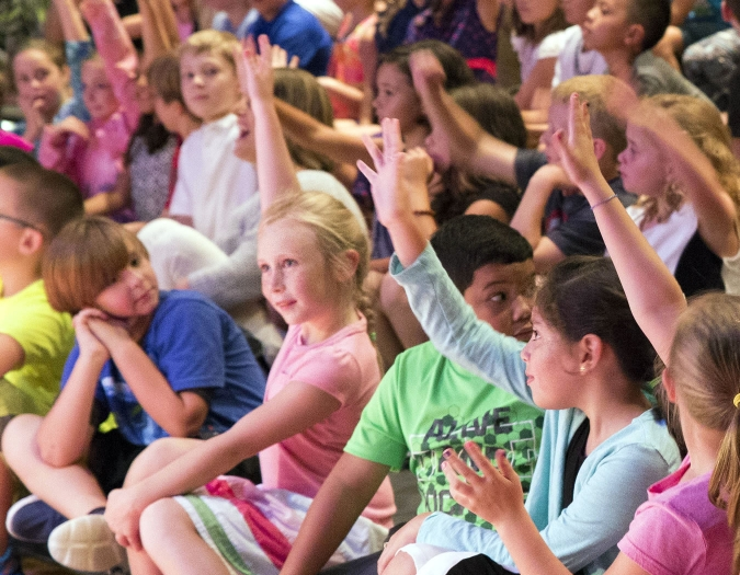 Image of students in the audience of Hayes Hall raising their hands during a Magic Carpet performance