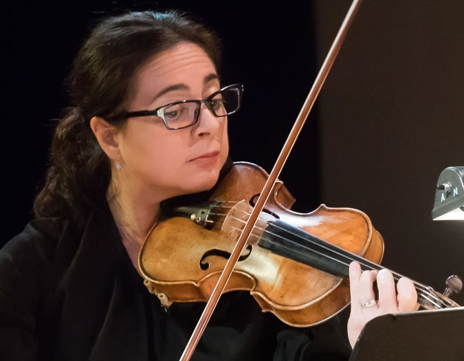 Image of Anne-Marie Terranova of the Naples Philharmonic on stage playing a violin during a performance