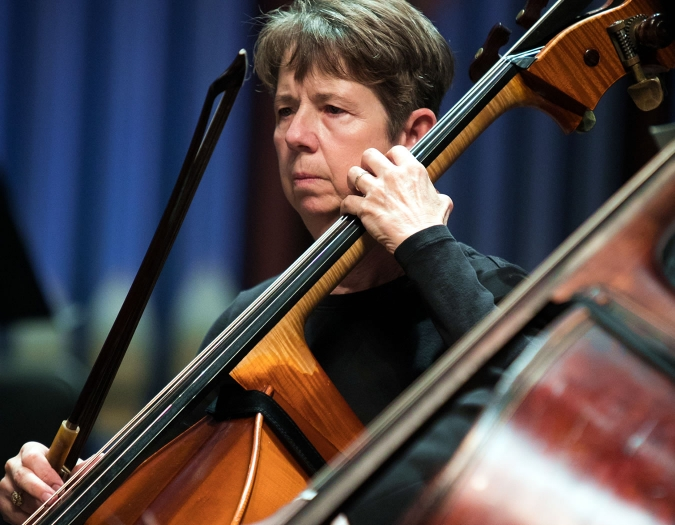 Image of Deborah Stehr of the Naples Philharmonic on stage playing a bass during a performance