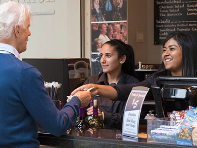 Image of cafe staff serving drinks and refreshments to patrons at the counter of the cafe