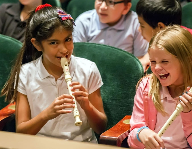 Image of students playing musical instruments in the seats of Hayes Hall during the education event Link Up