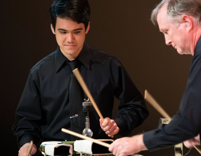 Image of John Evans and Brian Jordan of the Naples Philharmonic on stage playing percussion during a chamber music performance
