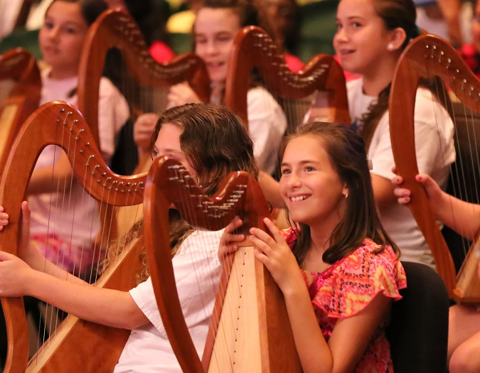 Image of students gathering with their instruments in the seats of Hayes Hall during the education event Link Up