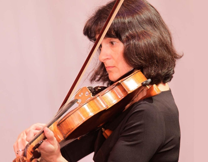 Image of Suzannah Chalik of the Naples Philharmonic on stage playing a violin during a performance