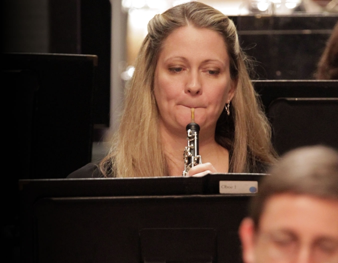 Image of Judy Christy of the Naples Philharmonic on stage playing oboe during a performance