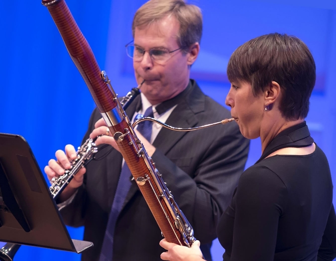 Image of Jenni Groyon Hill and Andrew Snedeker of the Naples Philharmonic on stage playing wind instruments during a chamber music performance