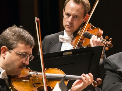 Image of Erik Berg and Patrick Neil of the Naples Philharmonic on stage playing violins during a performance
