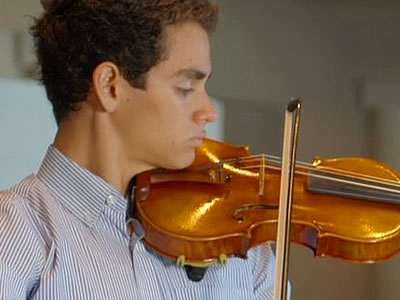 Image of a student musician performing on stage in a concert of the Naples Philharmonic Youth Orchestra