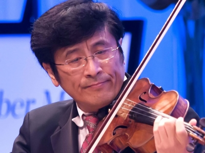 Image of James Zhang of the Naples Philharmonic on stage playing a violin during a performance