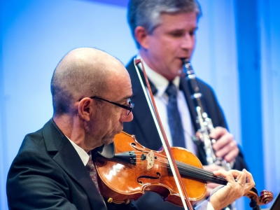 Image of members of the Naples Philharmonic on stage playing violin during a performance
