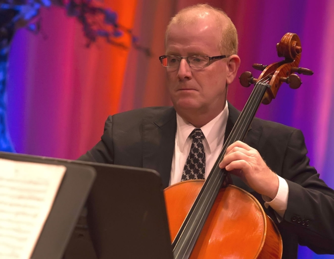 Image of Thomas May of the Naples Philharmonic on stage playing a cello during a performance