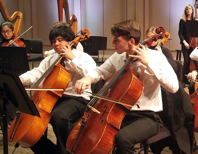 Image of student musicians performing on stage in a concert of the Naples Philharmonic Youth Orchestra