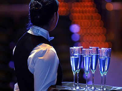 Image of an event services staff waiting with champagne glasses for incoming patrons during an event at Artis—Naples