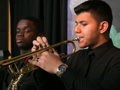 Image of a student musician performing on stage with the Naples Philharmonic Youth Jazz Orchestra