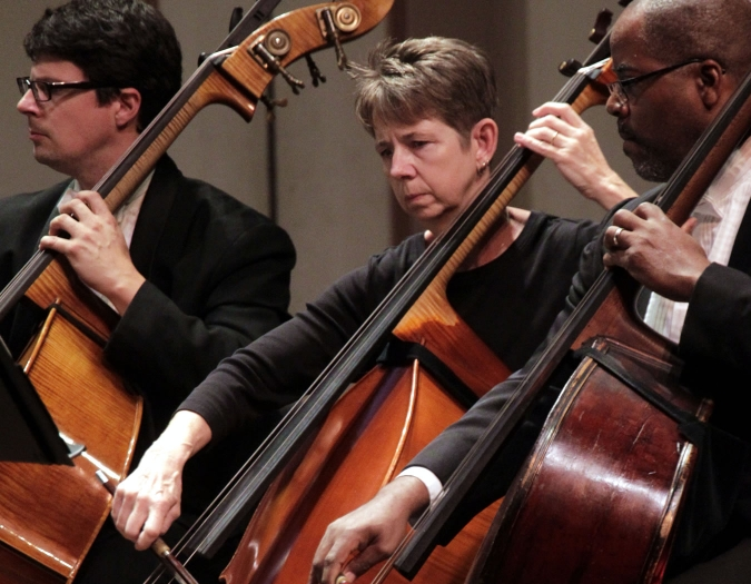 Image of Kevin G. Mauldin, Debra Stehr and Matthew Medlock of the Naples Philharmonic on stage playing a bass during a performance