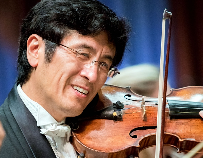 Image of James Zhang of the Naples Philharmonic on stage playing violin during a performance