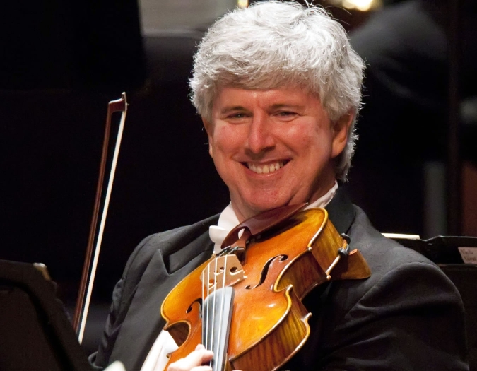 Image of James Griffith of the Naples Philharmonic on stage playing viola during a performance
