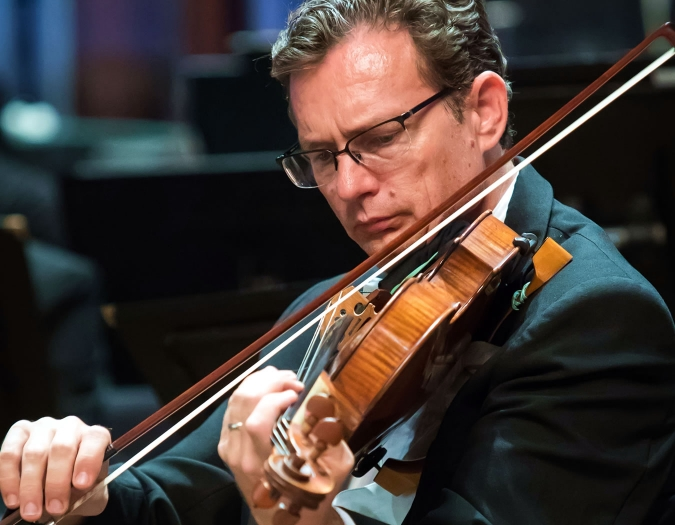 Image of Glenn Loontjens of the Naples Philharmonic on stage playing viola during a performance
