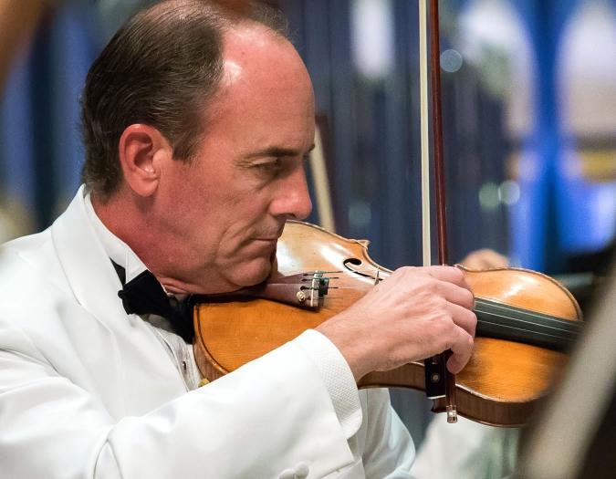 Image of Gregg Anderson of the Naples Philharmonic on stage playing violin during a pops performance