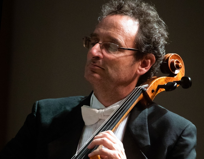Image of Eric Dochinger of the Naples Philharmonic on stage playing violin during a performance