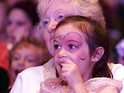 Image of a grandmother and her granddaughter in the audience watching a performance on stage