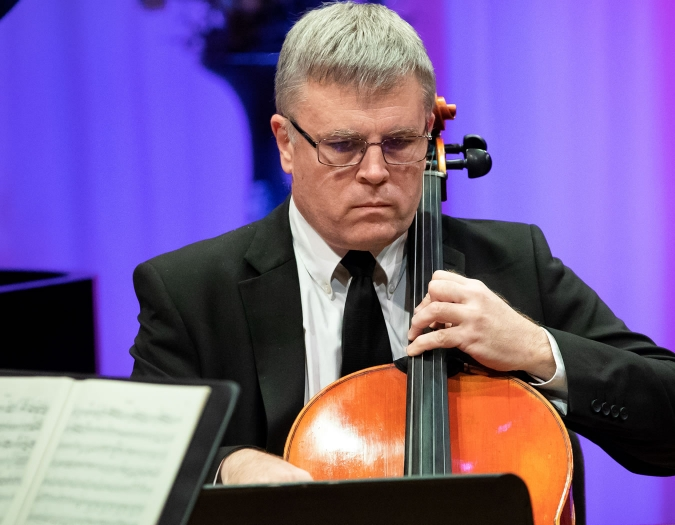 Image of John Marcy of the Naples Philharmonic on stage playing cello during a performance