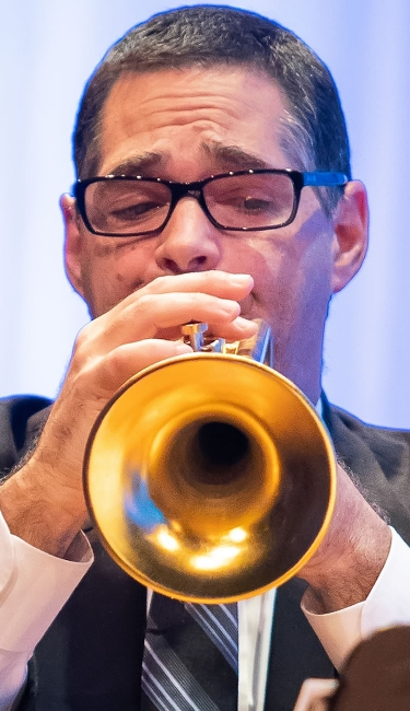 Image of Matthew Sonneborn of the Naples Philharmonic on stage playing trumpet during a performance