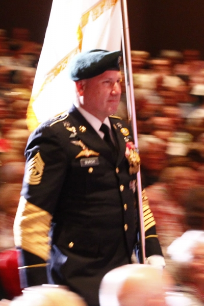 Image of a flag bearer of the American flag making his way through the audience to the stage during a performance of Patriotic Pops