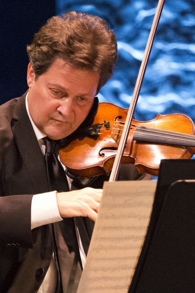 Image of Glenn Basham, concertmaster of the Naples Philharmonic on stage playing violin during a performance