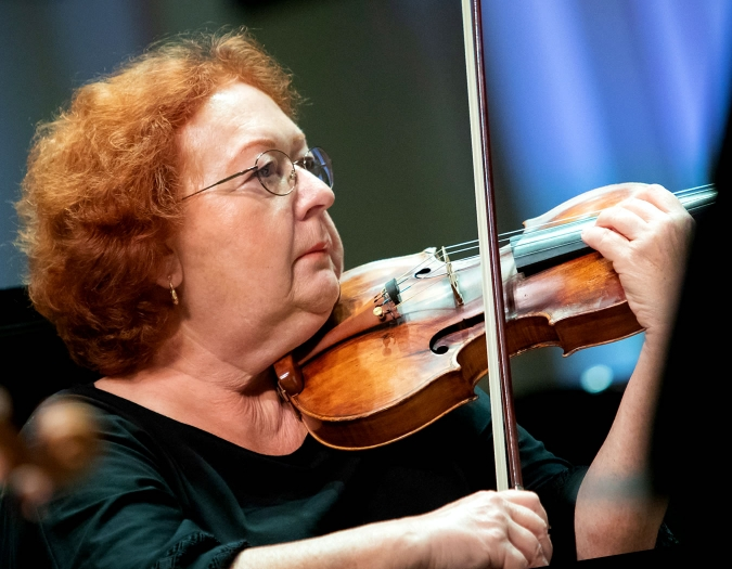 Image of Lyudmila Vainer of the Naples Philharmonic on stage playing violin during a performance