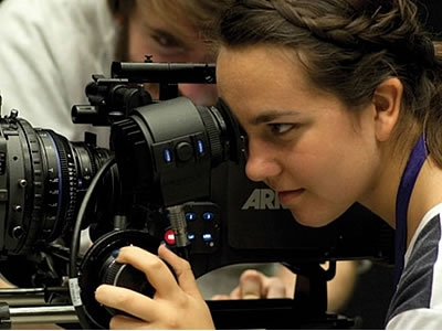 Image of a student filmmaker looking through a camera at her subject