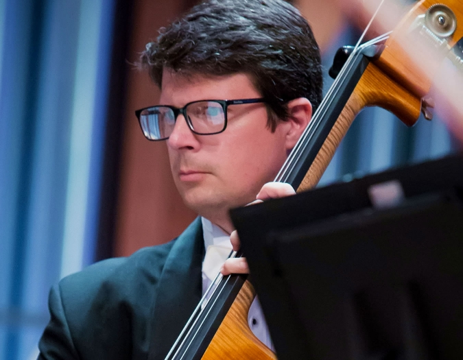Image of Matthew Medlock of the Naples Philharmonic on stage playing a bass during a performance