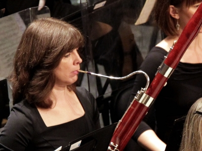 Image of Kristin Sonneborn of the Naples Philharmonic on stage playing a bassoon during a performance