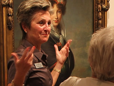 Image of a museum docent giving a walking presentation to patrons at The Baker Museum