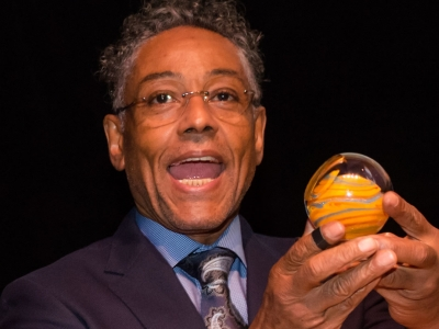 Image of actor Giancarlo Esposito holding up and accepting the Artis—Naples Award at the Naples International Film Festival