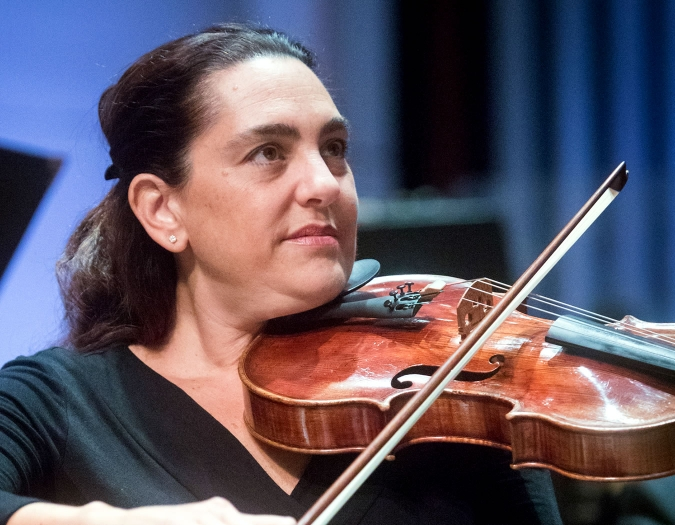 Image of Jessie Goebel of the Naples Philharmonic on stage playing violin during a performance