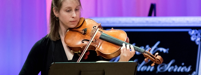 Image of Jane Mitchell of the Naples Philharmonic on stage playing violin during a performance