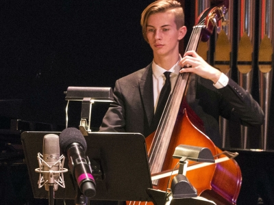 Image of a student musician performing on stage during a chamber concert of the Naples Philharmonic Youth Orchestra