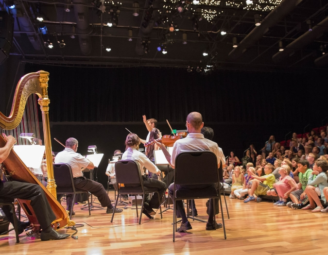 Image of musicians from the Naples Philharmonic on stage performing to an audience of children